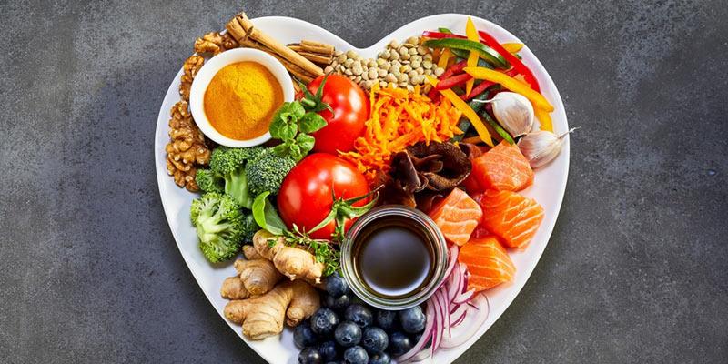 Herzförmiger Teller mit gesundem Obst und Gemüse