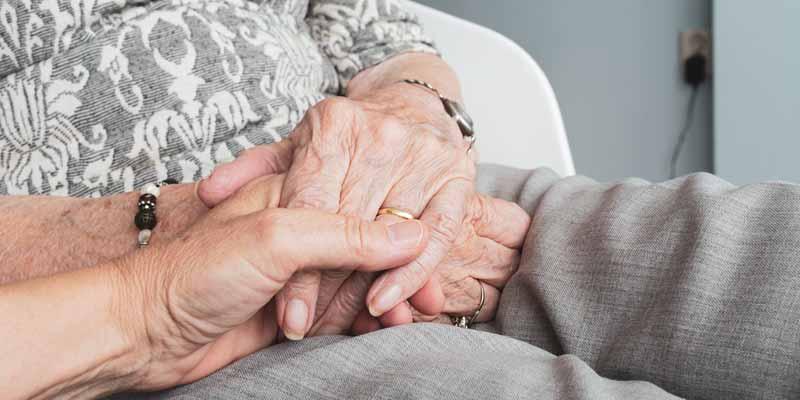 Hand von Seniorin wird gehalten