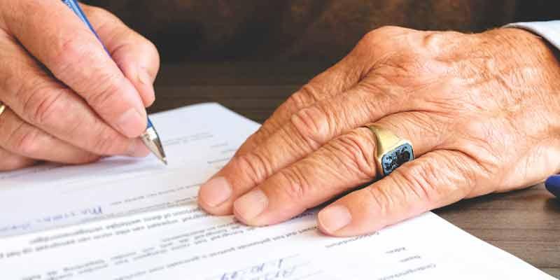 Senior unterschreibt ein Dokument