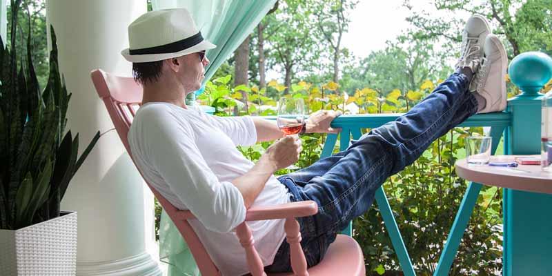Mann trinkt Wein auf Terrasse