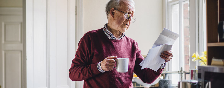 Senior hält ein Schreiben in der Hand