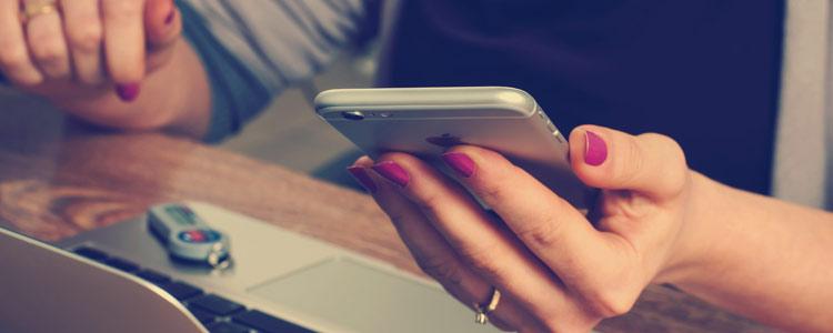 Frau mit Smartphone und Notebook am Schreibtisch