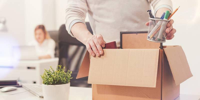 Mann packt Karton im Büro