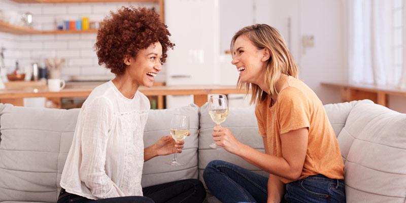 Zwei Frauen unterhalten sich bei einem Glas Wein