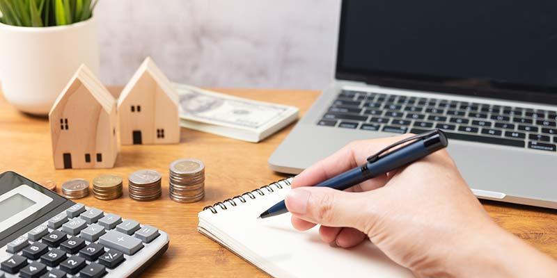 Schreibtisch mit Notizblock, Bargeld, Notebook und Taschenrechner