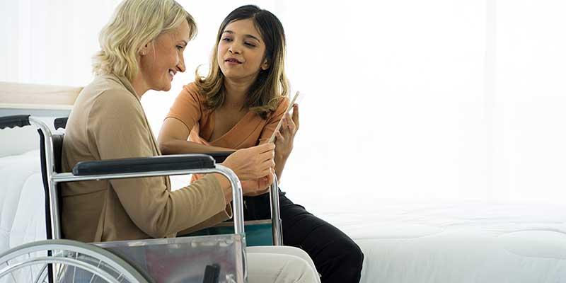 Frau im Rollstuhl in Begleitung einer weiteren Frau