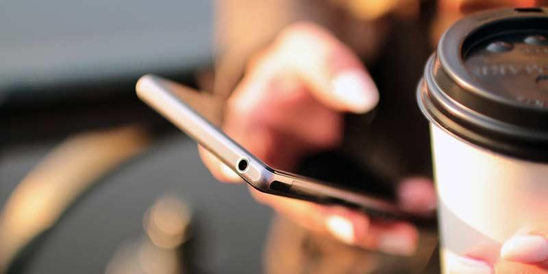 Smartphone und Kaffeebecher in der Hand