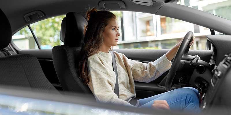 Junge Frau steuert ein Auto auf einer Straße
