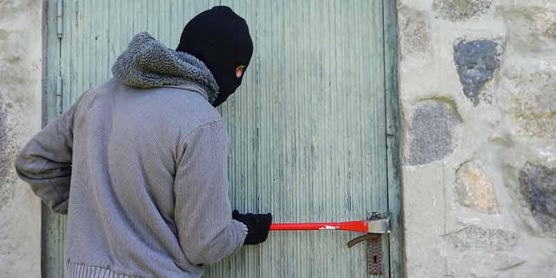 Ein Einbrecher versucht eine Tür aufzuhebeln
