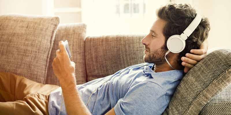 Mann schaut auf sein Smartphone und hat Kopfhörer auf