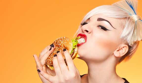 Junge Frau isst einen Burger