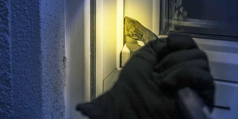 Ein Einbrecher versucht durch ein Fenster in eine Wohnung zu gelangen