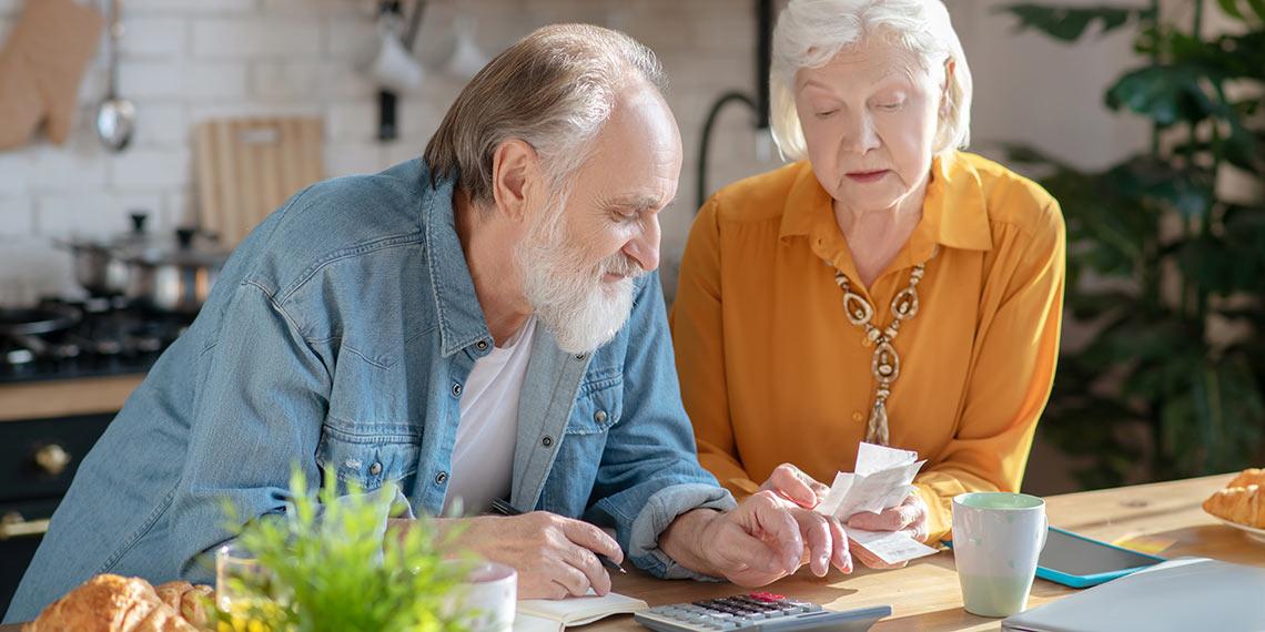 Rentner zählen Geld und bestimmen ihre Ausgaben.
