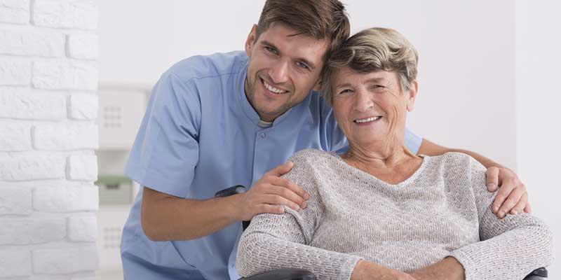 Pfleger gemeinsam mit Dame im Rollstuhl.