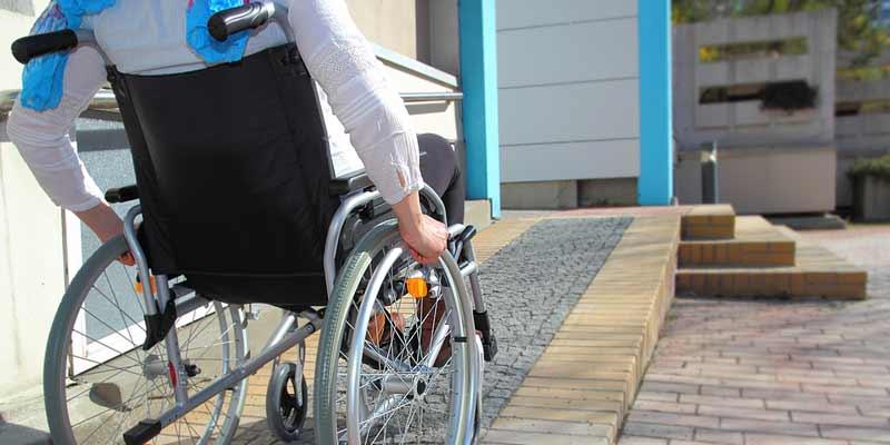 Rollstuhlfahrer auf einer Rampe Richtung Gebäude