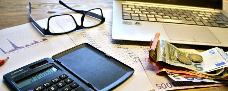 Schreibtisch mit Notebook, Bargeld, Taschenrechner und mehr