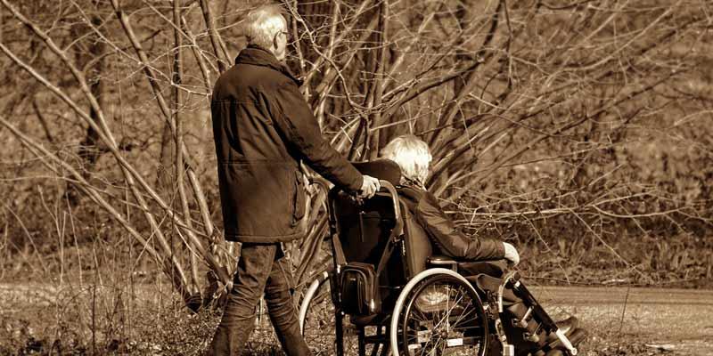 Mann schiebt Frau im Rollstuhl