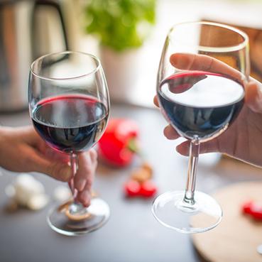 Zwei Personen stoßen mit Rotwein an