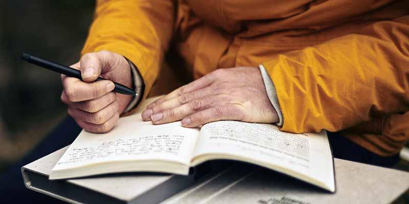 Person schreib in einem Buch