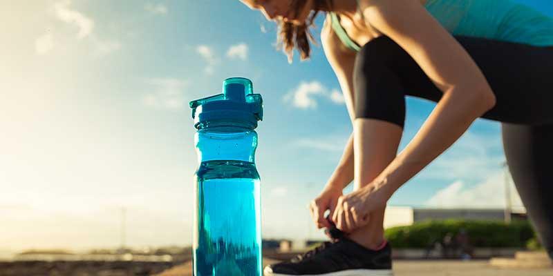 Junge Frau macht Sport im Freien und hat eine Wasserflasche dabei