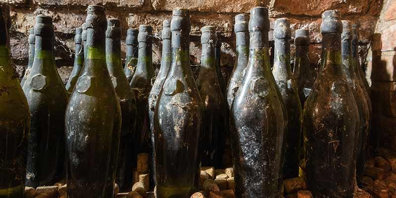 Verschmutzte Weinflaschen in einem Weinkeller