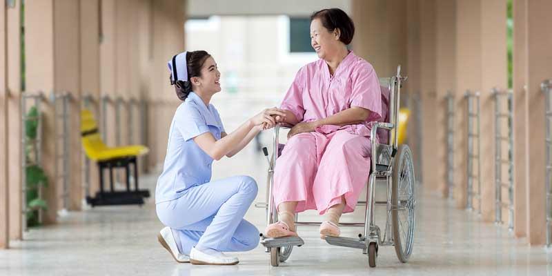 Frau im Rollstuhl wird liebevoll umpflegt