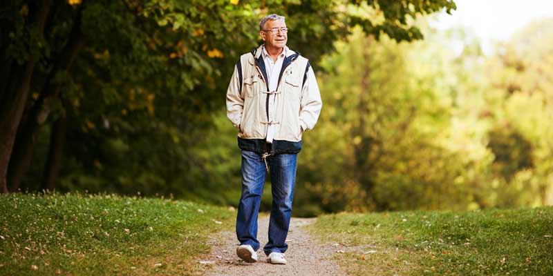 Mann spaziert durch einen Park