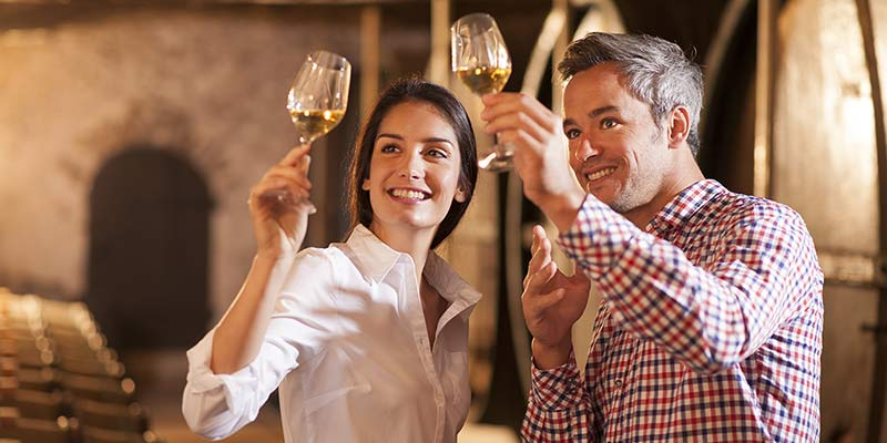 Frau und Mann begutachten Wein in einem Glas bei einer Weinprobe