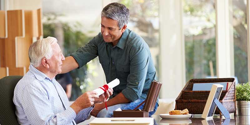 Älterer Mann überreicht seinem Sohn ein wichtiges Dokument.