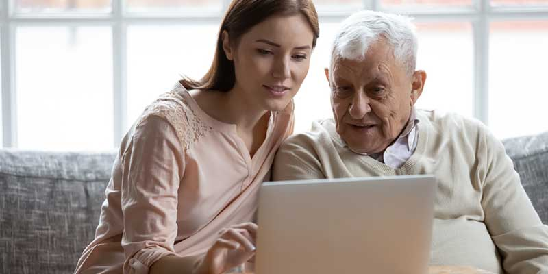 Enkelin und älterer Mann gemeinsam am Laptop.