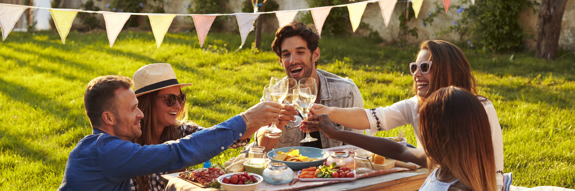 Freunde machen gemeinsam ein Picknick im Garten