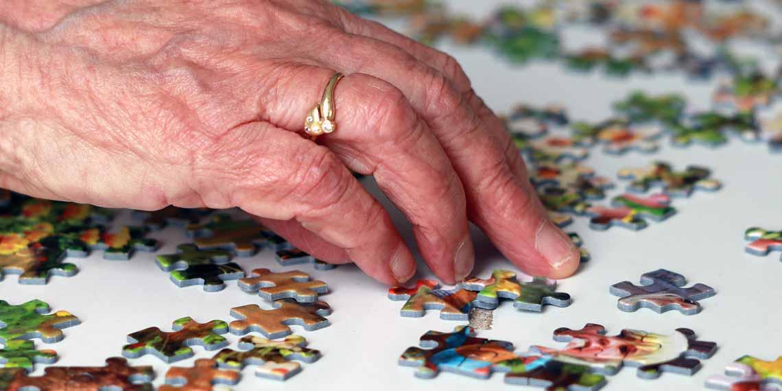 Seniorin beim Puzzeln