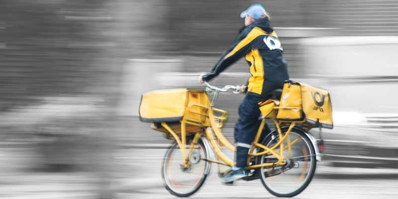 Postbote liefert Briefe mit einem Fahrrad aus