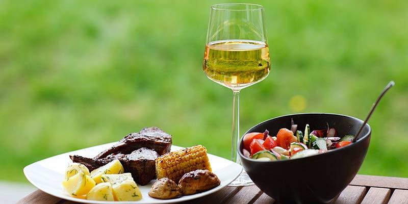 Sommerliches Essen mit Fleisch, Gemüse und Salat zusammen mit einem Glas Wein