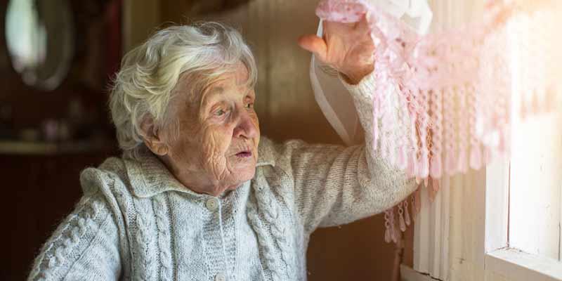 Seniorin schaut aus dem Fenster