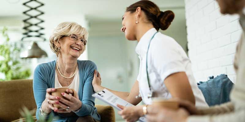 Glückliche ältere Dame vertieft in Gespräch mit Krankenschwester.