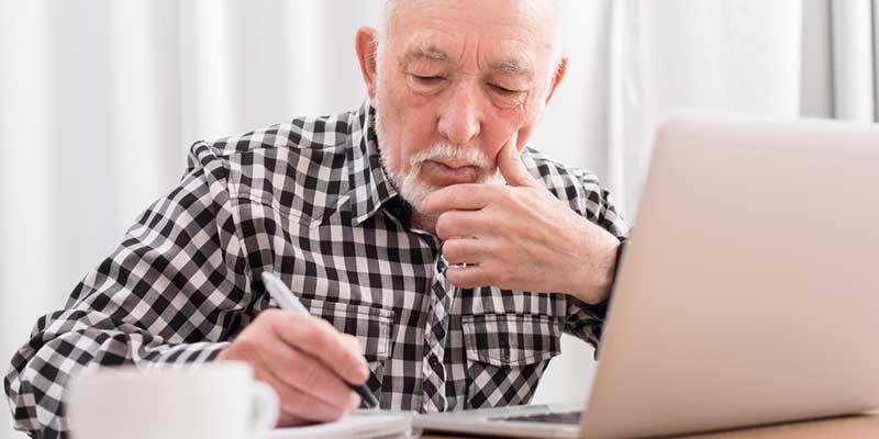 Älterer Herr macht sich Notizen am Laptop.