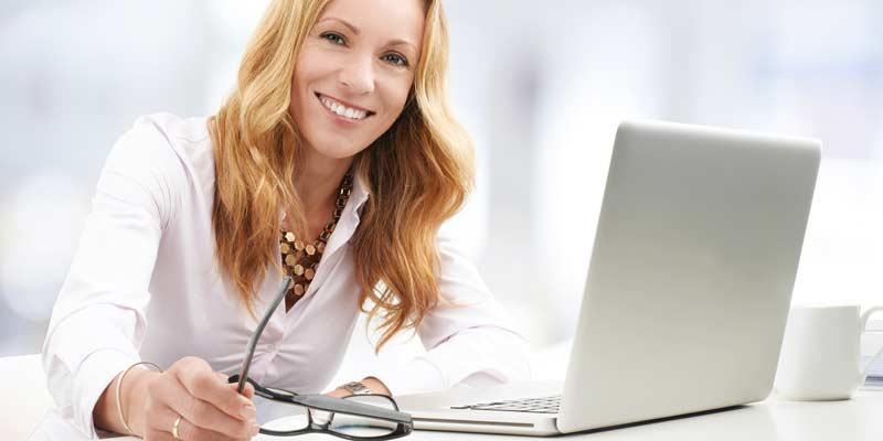 Geschäftsfrau sitzt vor einem Notebook