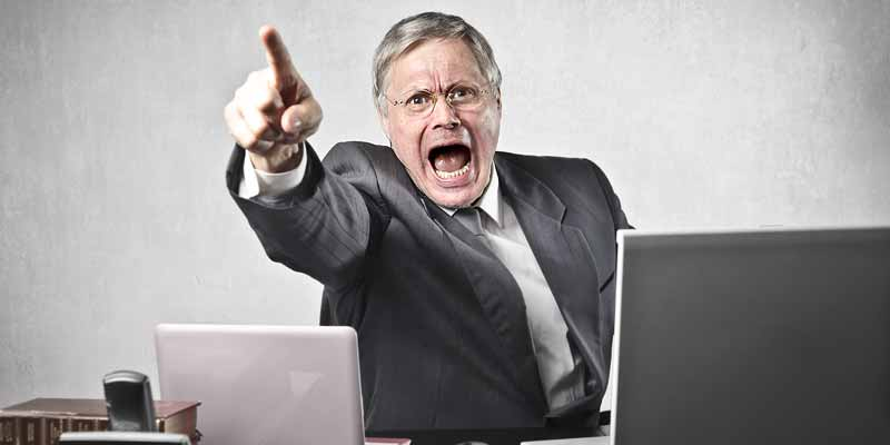 Wütender Mann hinter einem Schreibtisch