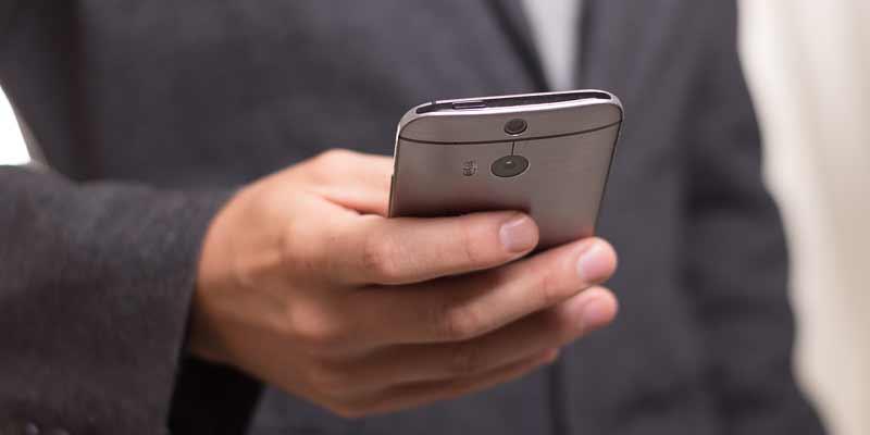 Mann hält ein Smartphone in der Hand