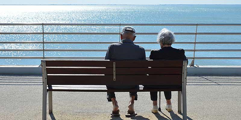 Paar sitzt auf einer Bank am Wasser