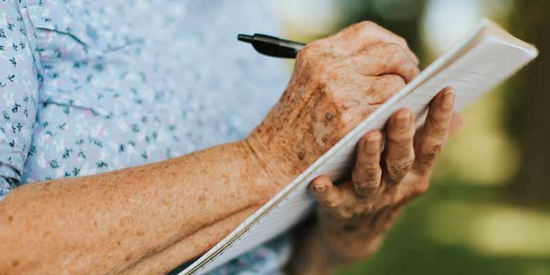 Senior schreibt auf einen Block