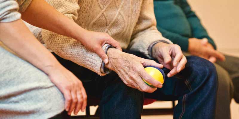 Senior hält einen kleinen Ball in der Hand