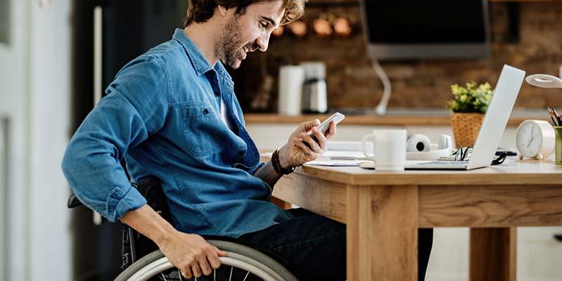Mann im Rollstuhl sitzt am Schreibtisch mit Smartphone und Notebook