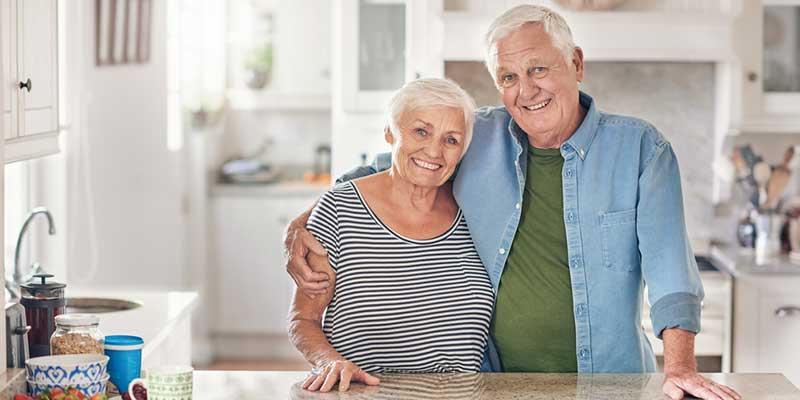 Glückliches älteres Paar steht Arm in Arm in der Küche.
