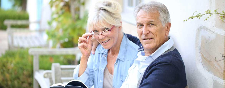 Paar sitzt auf einer Bank vor dem Haus