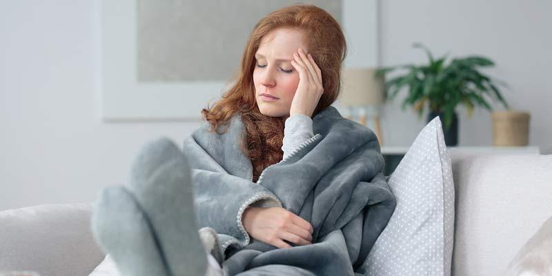 Frau liegt mit Decke auf einem Sofa