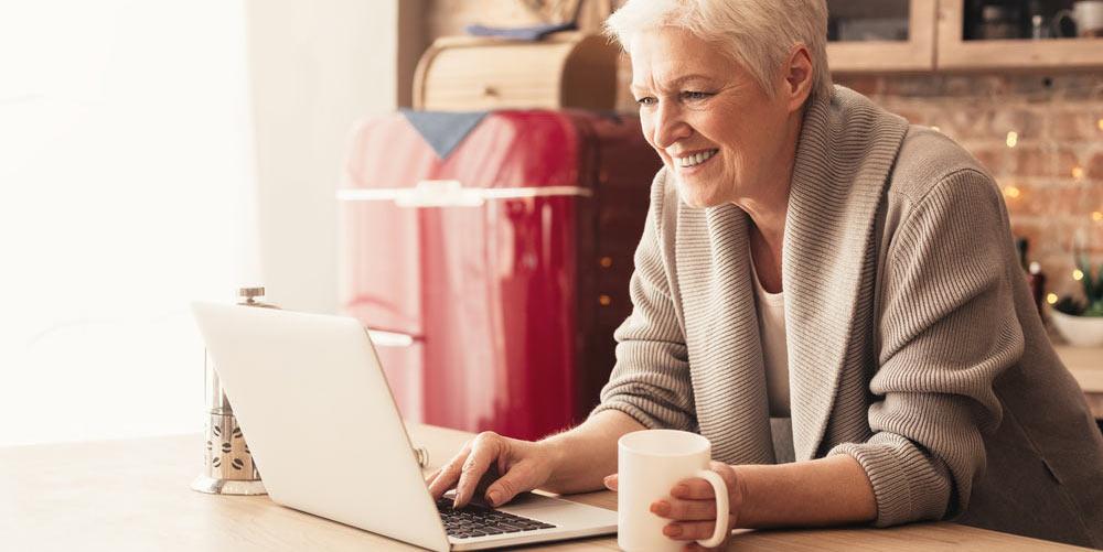 Ältere Dame sitzt am Tisch und blickt glücklich auf ihren Laptop.