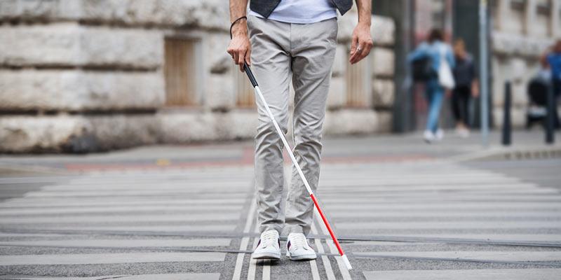Mann mit Blindenstock auf Straße