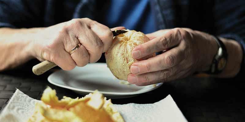Seniorin schält eine Orange